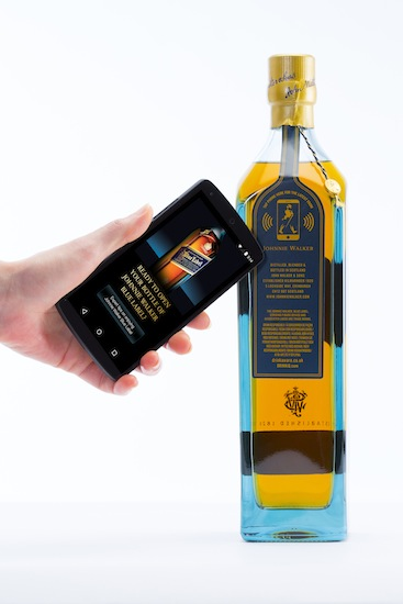 Photo: a user taps the bottle with an NFC smartphone to get information